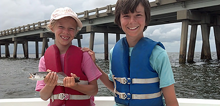 Two boys with fish caught aboard Rock On Charters.