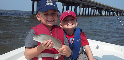 Two young boys with fish caught aboard Rock On Charters.